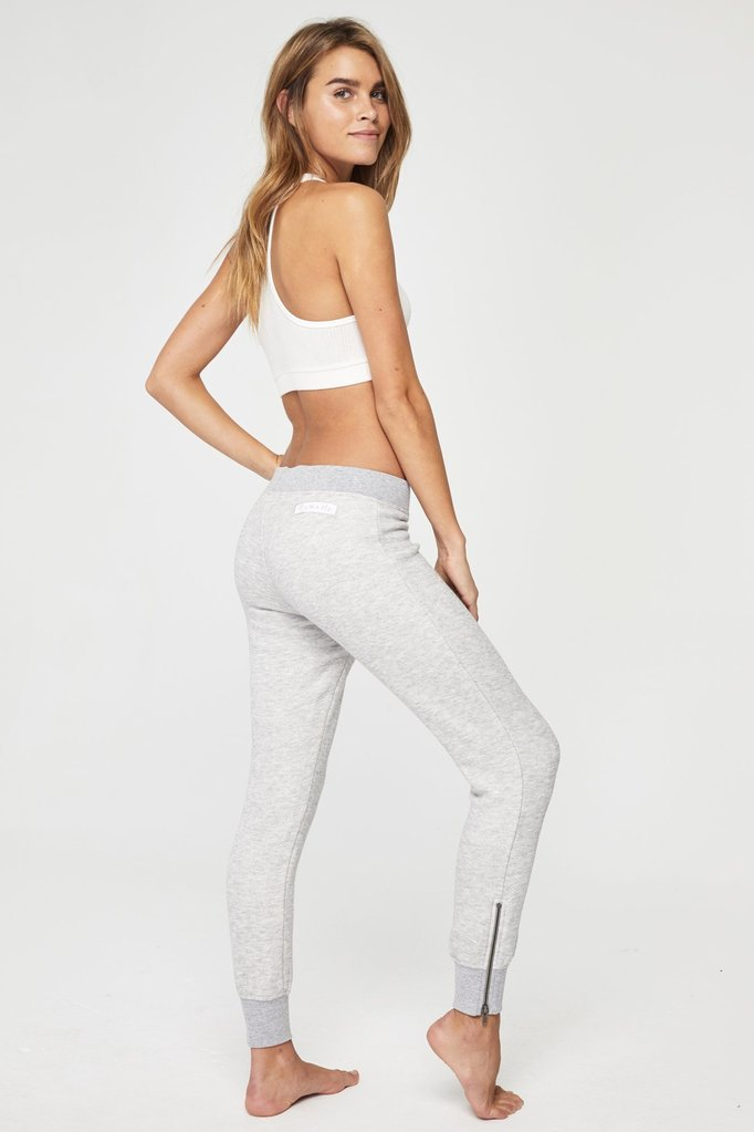 "Model is wearing light grey slim sweatpants with slim waist band and a zipper detail on the ankle that reaches mid calf. The pants feature a patch on the right bum cheek that says ""Namaste"" in light pink."