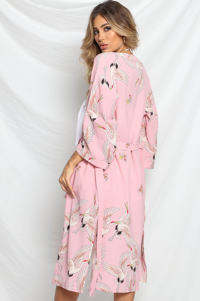 Model is wearing the Good Fortune Kimono by Prem. The kimono is midi length, baby pink that features white doves all over. Slits along the sides of the kimono allow it to drape nicely over your curves.