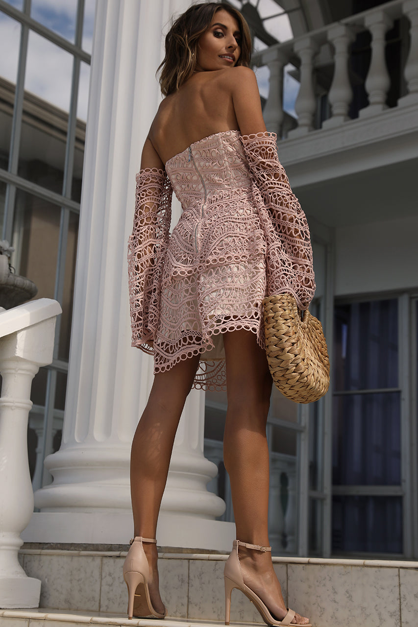 Model is wearing off-shoulder, blush pink, long-sleeve, cinched waist, lace mini dress.