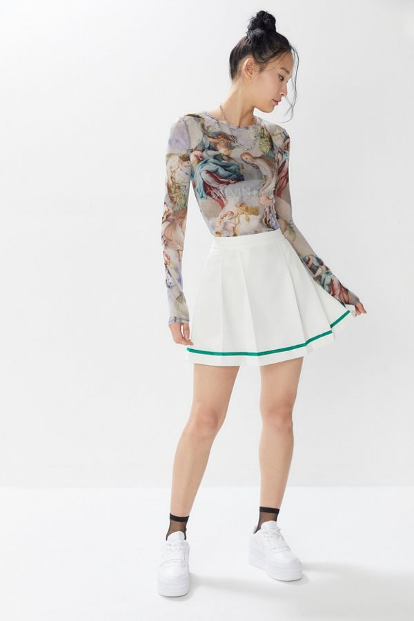 Model is wearing a English Factory white pleated mini skirt. The Serena pleated mini skirt is high waisted and short, the hemline reaches about 4 inches from the knee. The skirt also features a dark green vertical stripe an inch above the hemline. With a side Zip closure.
