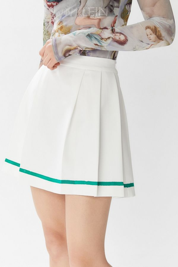 Model is wearing a English Factory white pleated mini skirt. The Serena pleated mini skirt is high waisted and short, the hemline reaches about 4 inches from the knee. The skirt also features a dark green vertical stripe an inch above the hemline.