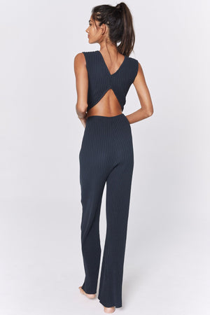 model wears a vintage black ribbed jumpsuit with an open back and a twist in the fabric exposing the stomach