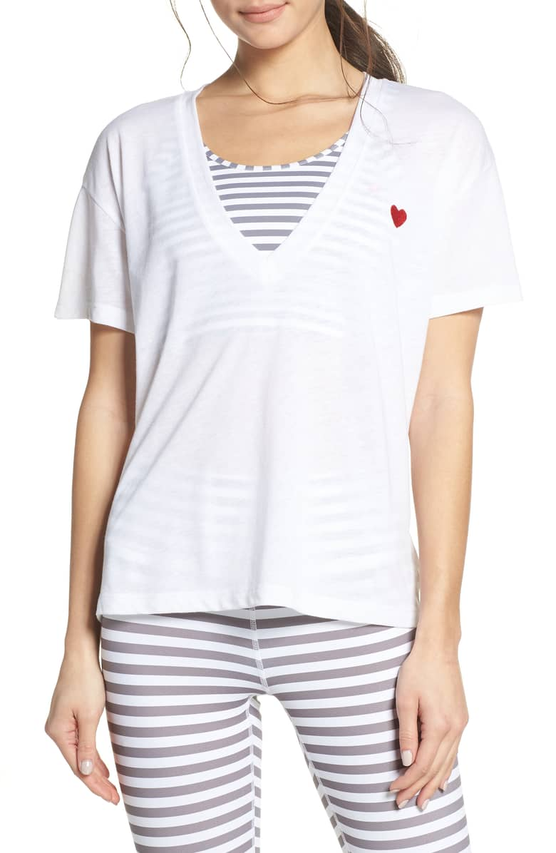 Model wearing white n-neck t-shirt with an embroidered red heart on the left side.