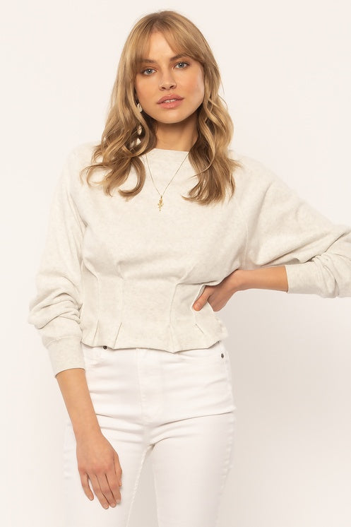 UNIKONCEPT: Lifestyle boutique; image shows a white pebbled fleece peplum sweater by Amuse society. The Devon peplum is a crewneck styled cropped sweater with small pleats around the waistline to give the illusion of a peplum cut.