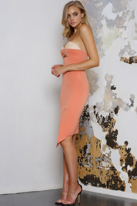 Model is wearing orange, body con, strapless, midi-length runaway dress. The Milan dress comes with asymmetrical hemline. The dress features a sweetheart neckline with vegan leather bust detailing, cut out at the front and side pockets.