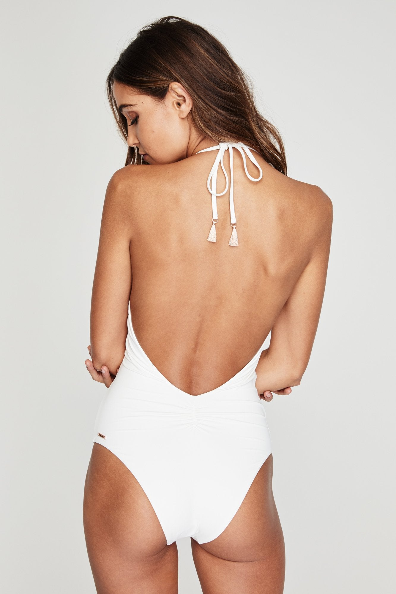 Back view of model wearing a white one piece, low scoop-back swimsuit, with a halter spaghetti tie, and cheeky cut bottoms.
