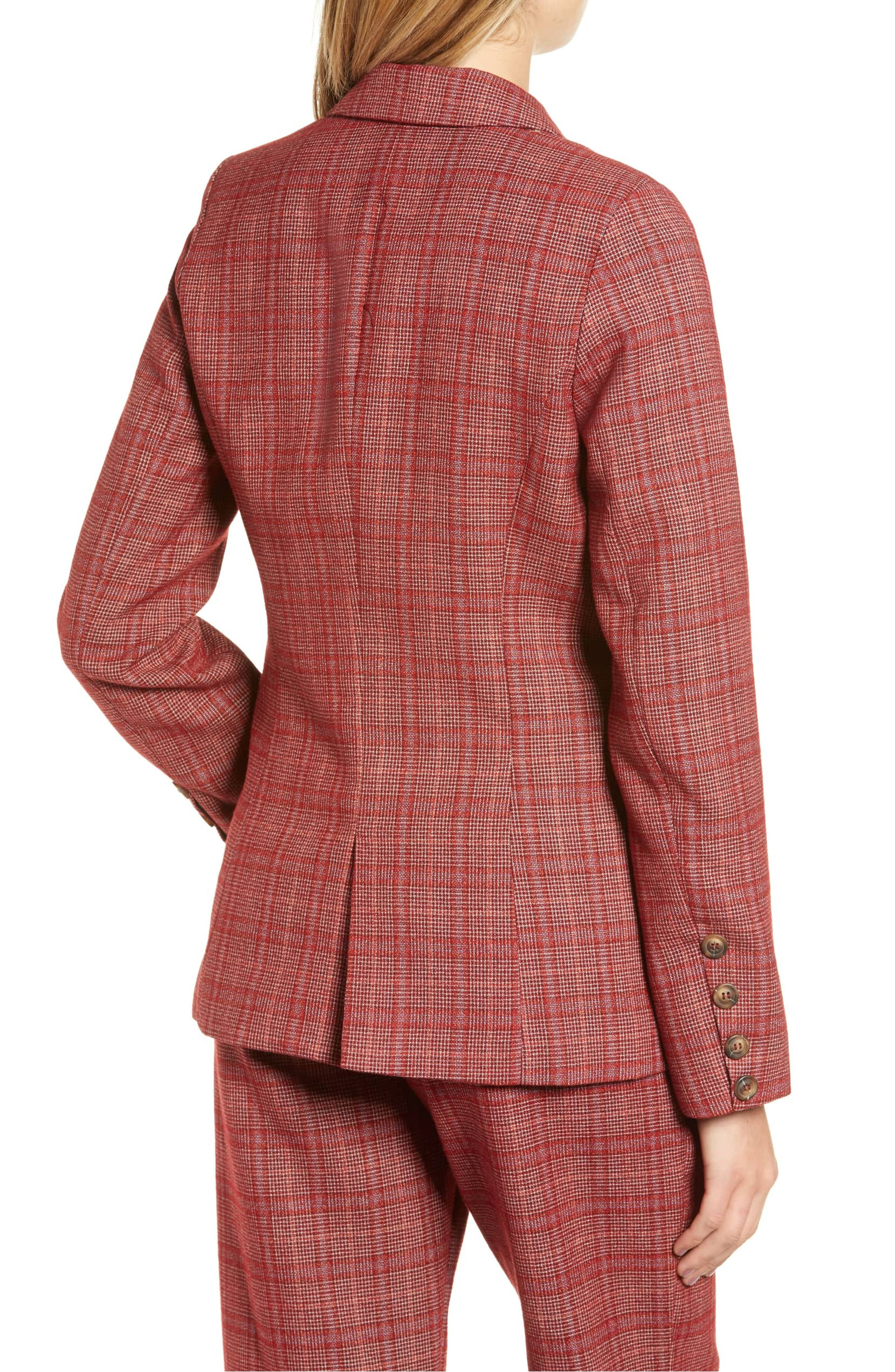 Model is wearing red plaid, double breasted, fitted blazer with brown buttons. The blazer features pockets and a back vent for added movement.