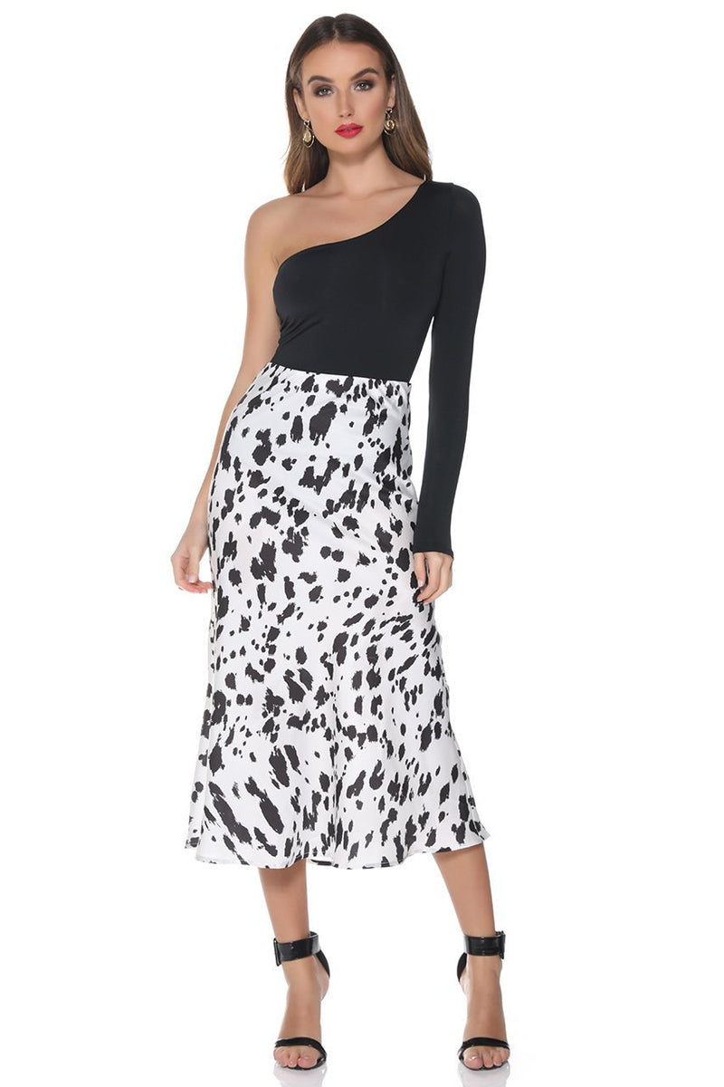 UNIKONCEPT: Lifestyle boutique; image shows a white based slip skirt with a black cow print pattern. Runaway created the perfect skirt when making the Indiana slip skirt it features a side zipper for easy dressing and removal, it is midi length and has a black and white cow print throughout.