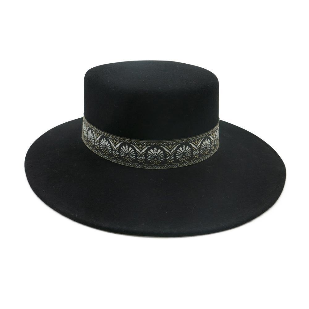 UNIKONCEPT Lifestyle boutique; image shows the Coachella Felt Boater in black by Ace of Something. This black wool boater features a gold patterned band trim around the base of the hat.