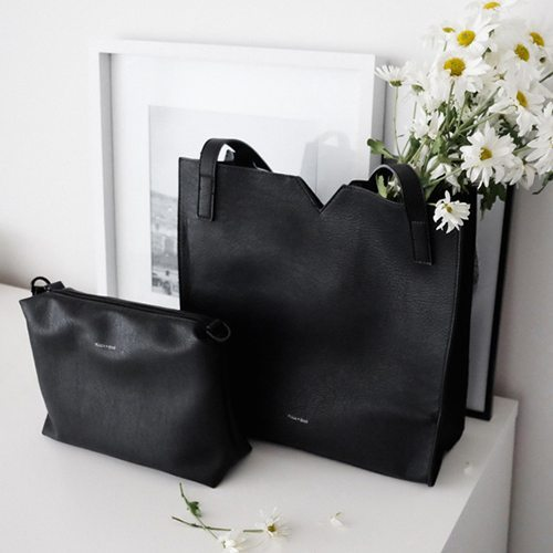 Black, faux leather soft, shoulder bag that features a small triangle cut out in the middle of the top line. The bag has a small inner pouch that comes with a detachable long strap to be used as a crossbody strap.
