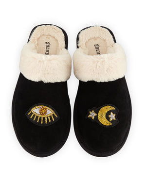UNIKONCEPT Lifestyle boutique: Pictured here is a pair of open back, black cowhide soludos slippers. The celestial cozy slipper featuring a faux fur creme lining. The slide-on slippers feature an eye on the right slipper and a moon with stars stitched into the instep.