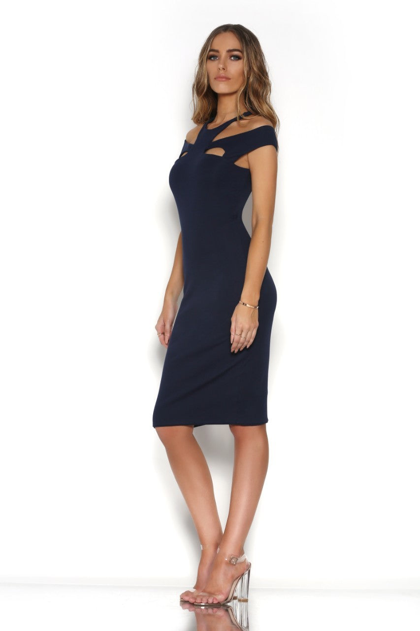 Model is wearing a navy blue, body con, mini dress with abstract cut outs around neckline. The dress features cap sleeves and high neck with cutouts at the shoulder and just above chest.