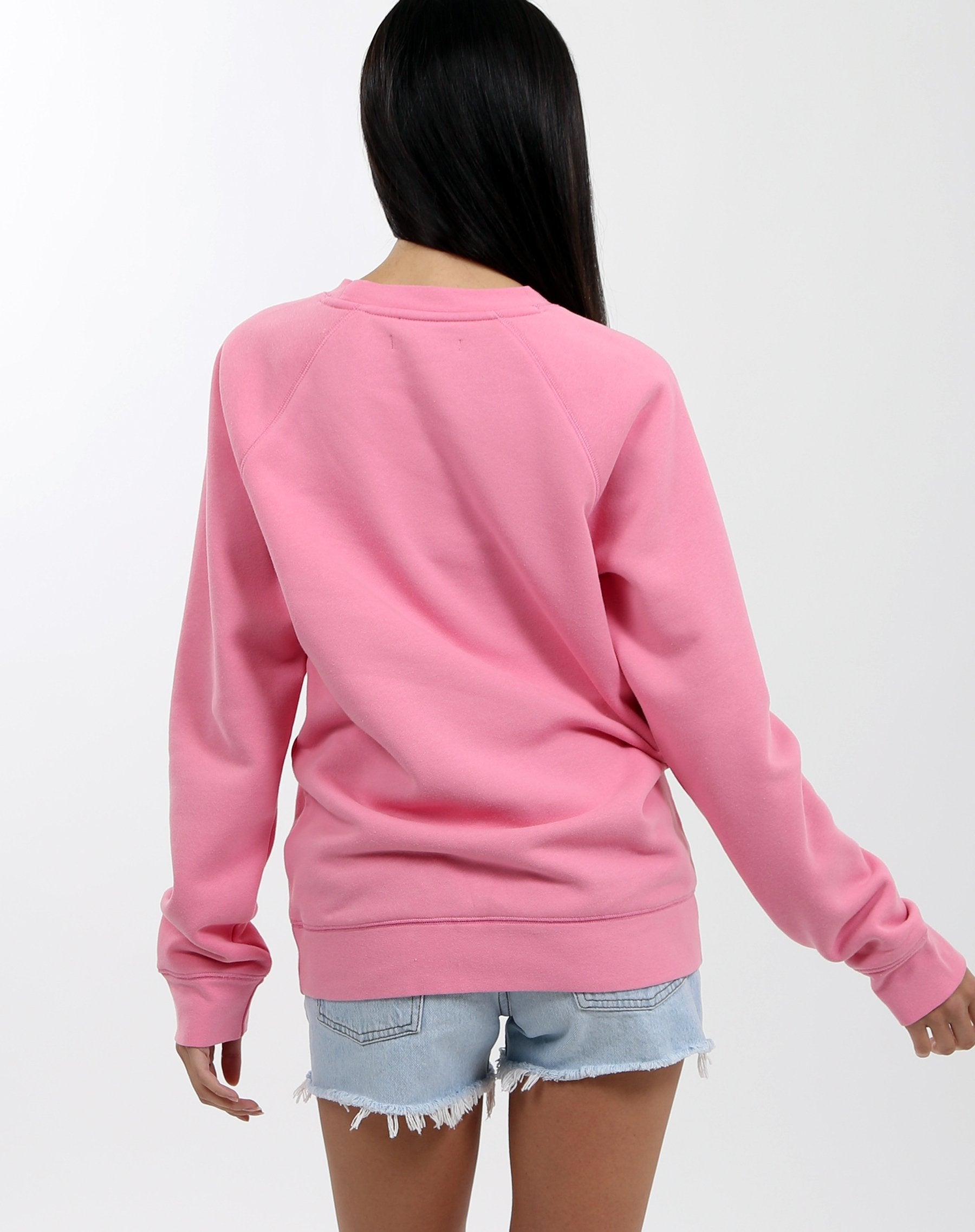 "Model is wearing Brunette the Label, Brunette crew neck sweater in Hot Pink. The crew sweater, in big white lettering across the chest says ""Brunette""."