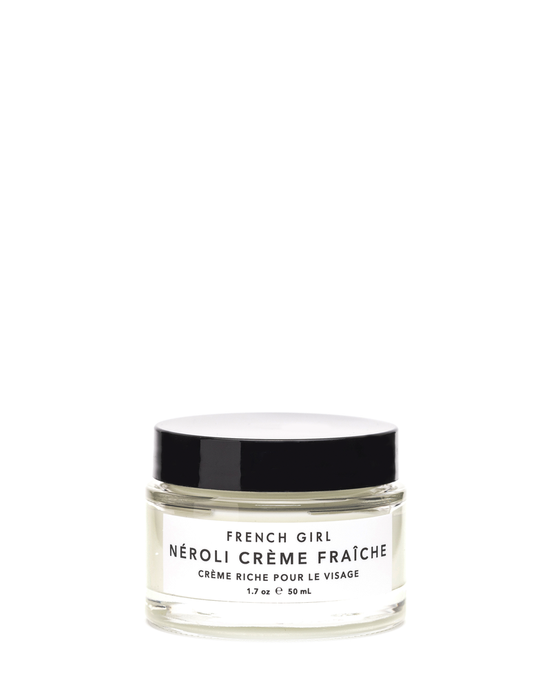 "A front view of a glass jar with a black lid and a white label that reads ""French Girl, Neroli Creme Fraiche, 50ml"""