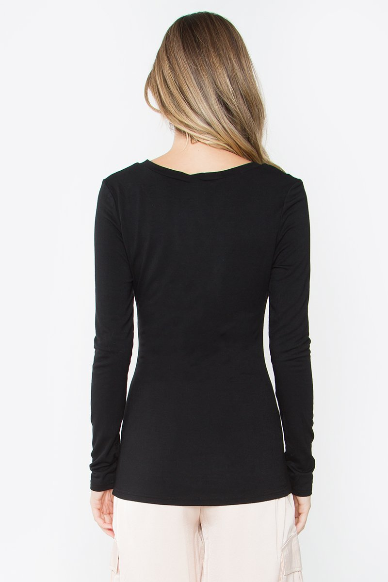 Model is wearing a long-sleeve, v-neck black top. View from back.