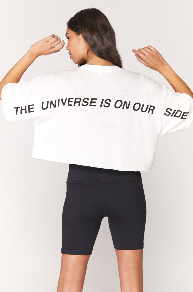 "UNIKONCEPT Lifestyle boutique; image shows the Universe Solstice Cropped Tee by Spiritual Gangster. This oversized, boxy, crop tee features a crew neck and is white. Along the back of the tee in all black caps is written ""THE UNIVERSE IS ON OUR SIDE"""