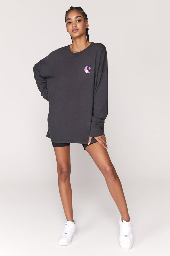 "UNIKONCEPT Lifestyle boutique; image shows the Revolution Oversized Tee by Spiritual Gangster. This classic crewneck long sleeve tee is black with metallic purple detailing. On the front chest is a small moon and star, while the back features a mural of hands, a sun and says ""LOVE REVOLUTION""."