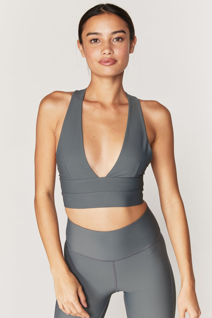 UNIKONCEPT: Lifestyle boutique, Model is wearing a olive green spiritual gangster sports bra. The Good vibes sports bra features a low plunge v-neckline, thick criss crossed razorback straps and a thick waistband to insure support and comfort.