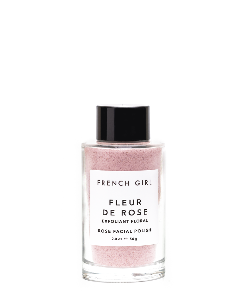 Picture shows a glass bottle with pink granules used for exfoliating the face, comes with a black lid