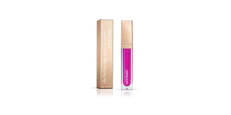 UNIKONCEPT lifestyle boutique: Image shows a bottle of lipgloss by Sara Happ. The fuchsia slip is dark pink, almost purple shade the bottle comes a gold lid and a clear bottle so you can see the shade of the lip colour.