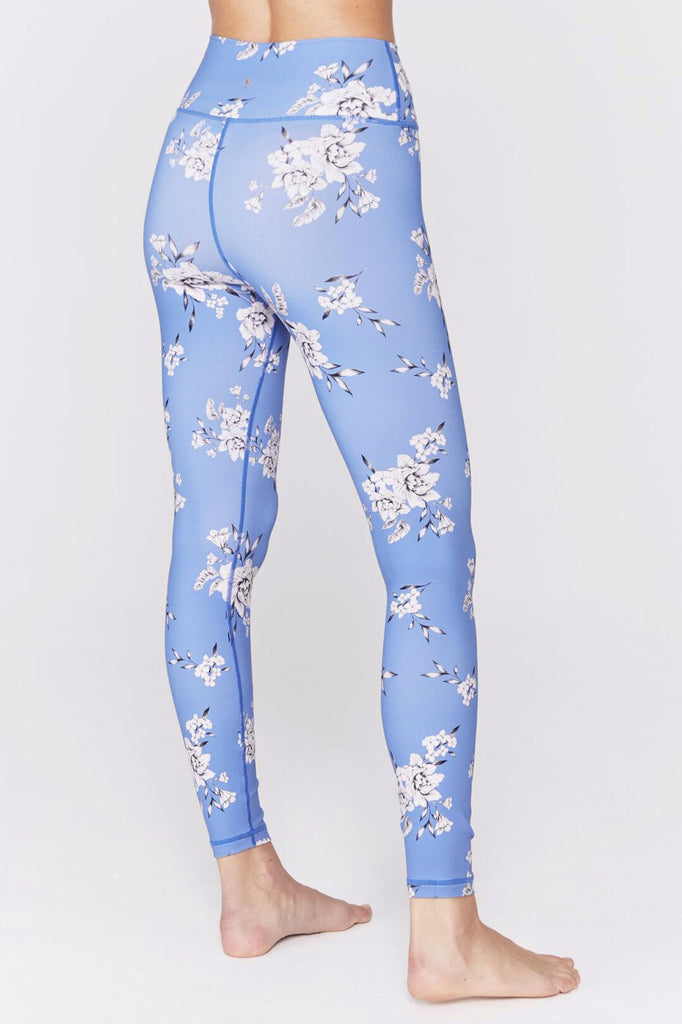 Model is wearing a pair of spiritual gangster leggings. The perfect high waisted blue floral legging is high waisted with a blue base and white delicate flowers.