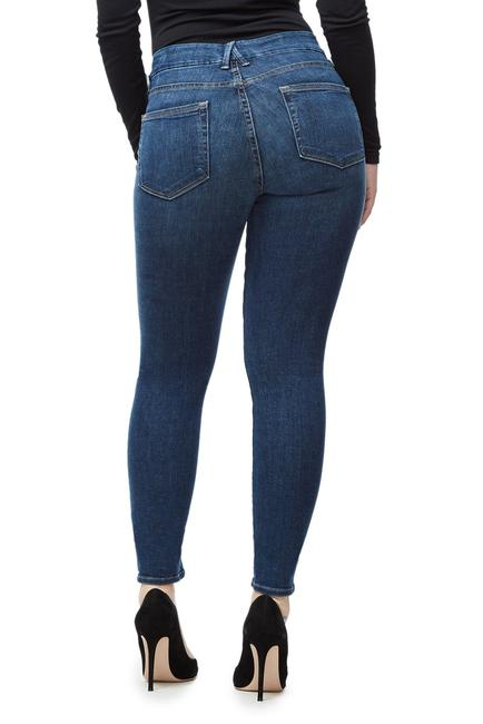 Model wears a pair of dark blue Good American denim. The Good legs denim is made for accentuating toned legs and a shapely bum.