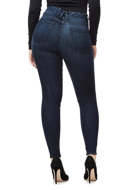 Model wears a pair of dark blue Good American denim. The Good waist denim is made for accentuating a smaller waist and a shapely bum. This pair of denim is shorter in length than the regular Good American jean.