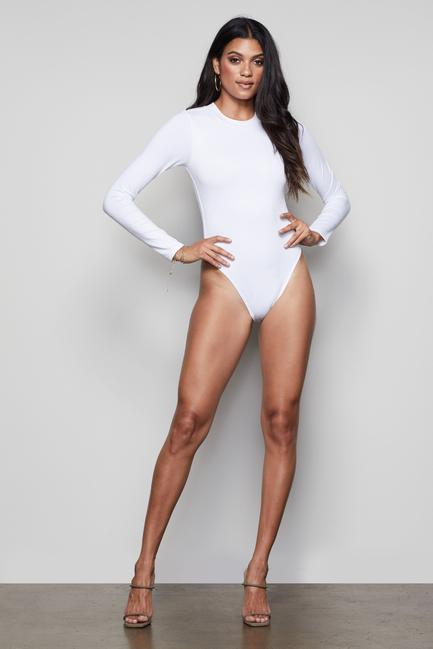 UNIKONCEPT Lifestyle boutique: image shows the Crewneck Bodysuit by Good American in white. This fitted, long-sleeve, crew neck style bodysuit is a staple in your wardrobe. Featuring a button clasp along the underwear portion of the bodysuit, it can be put on or removed extremely easily.