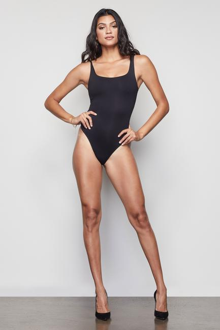 UNIKONCEPT Lifestyle boutique: this image shows the Black Tank Bodysuit by Good American. This ultra-soft matte black bodysuit is a tank top with a low cut front and back squared neckline. The bodysuit is a clasped thong cut allowing for over head dressing.