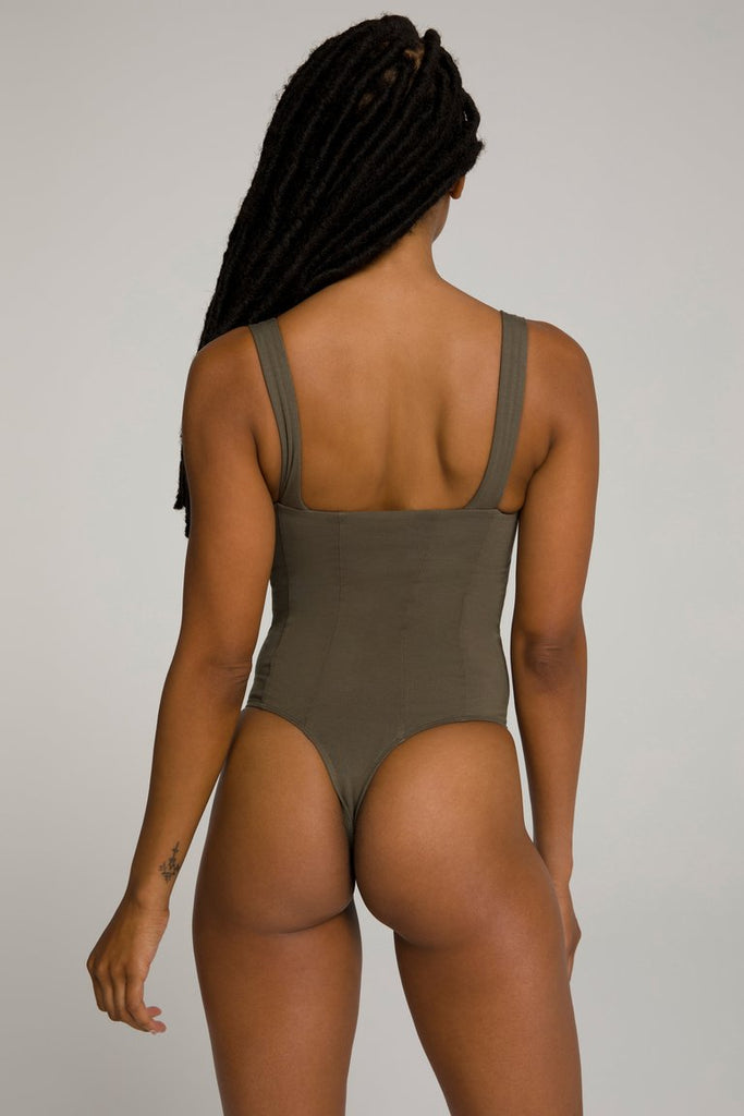 UNIKONCEPT LIFESTYLE BOUTIQUE: This model is wearing the Contoured bodysuit by Good American in the colour sage. This bodysuit has contour stitching on the front adding visual enhancement and thick straps for extra comfort. It also features a button clasp along the underwear portion.