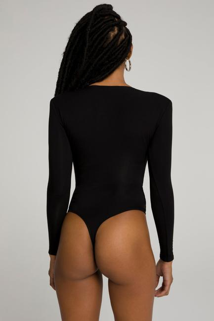 UNIKONCEPT LIFESTYLE BOUTIQUE: This model is wearing the Power Shoulder bodysuit by Good American in the colour black. The bodysuit has a deep V neckline with long sleeves and shoulder pads. It also features a button clasp along the underwear portion.