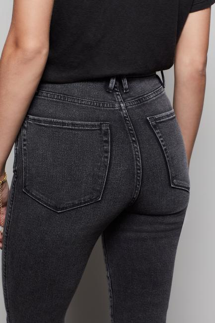 UNIKONCEPT: Image shows a pair of Good American denim. The Good Curve skinny denim with a raw edge features a very high waisted skinny jean, it is grey/black acid washed in colour and features a raw edge at the end of each leg.