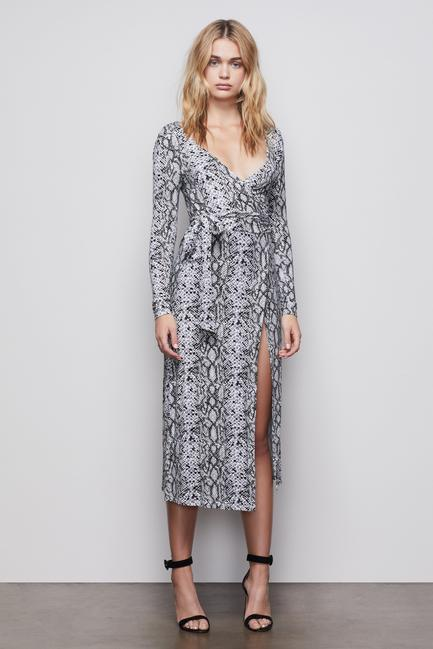 UNIKONCEPT Lifestyle boutique: image shows the Run Around Wrap Dress by Good American. This long-sleeve, ultra low v-neck, midi length, wrap dress is unbelievably soft and features the most flattering silhouette ever. The wrap detail cinches your waist perfectly and can be tied wherever you prefer the bow detail to sit. The fabric crosses of in the front allowing for a slit detail to run up the thigh. The fabric is a grey and black snake skin print.