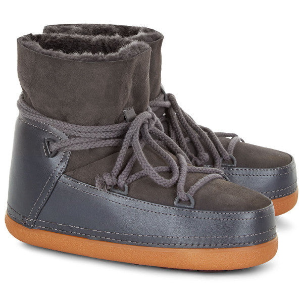 Pictured here is a pair of light grey winter boots with camel coloured rubber bottoms. The boots feature a lace up and around the ankle light grey tie and water resistant shiny material just above the rubber sole. The boots are lined with shearling and have a leather instep.