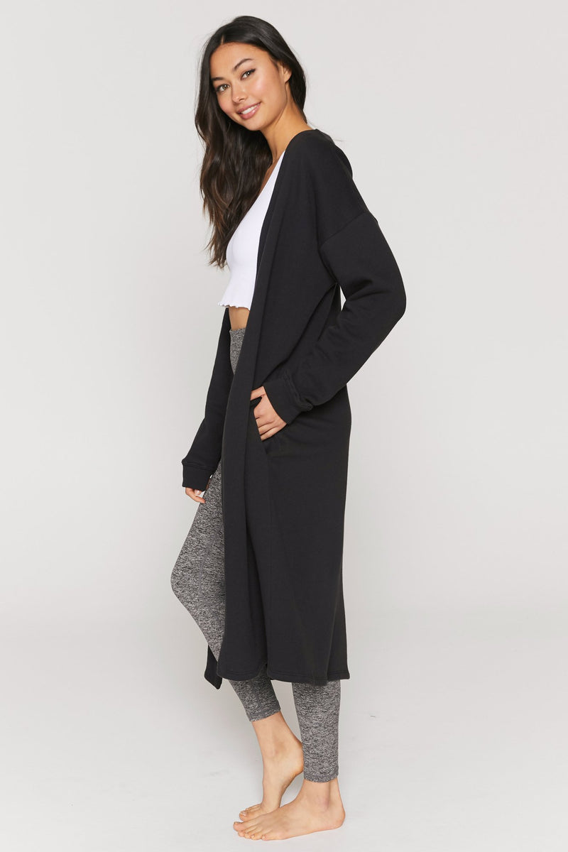 UNIKONCEPT: Lifestyle boutique; Image shows a vintage black oversized duster. The Layer up fleece Cardigan by spiritual gangster is a thick vintage black cardigan it goes to about knee length and features an inner fleece side and two side pockets.