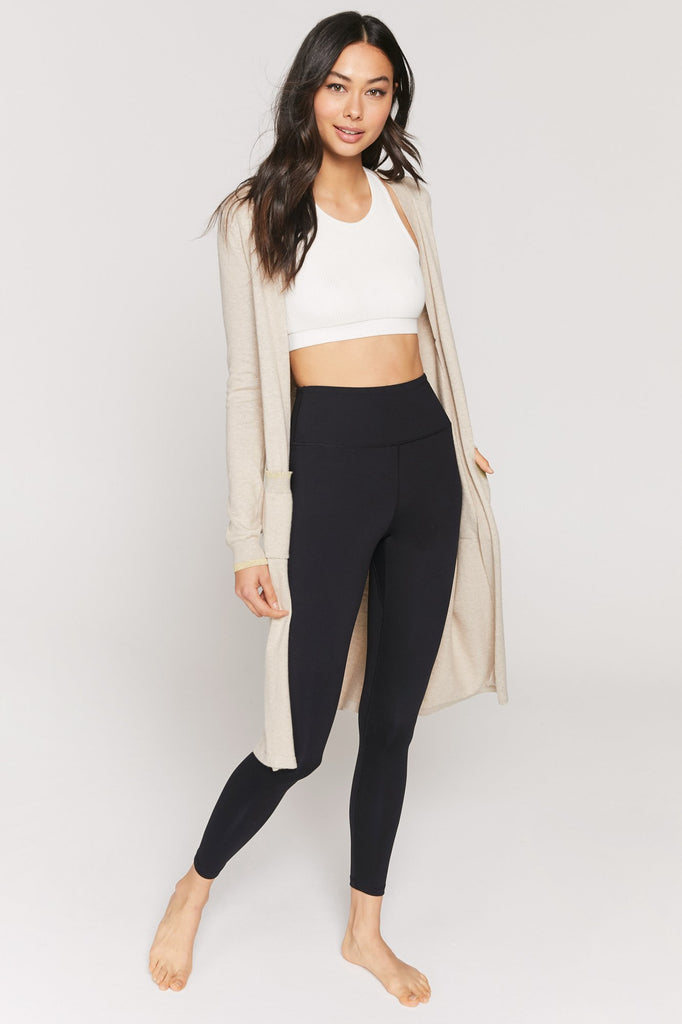 UNIKONCEPT: Lifestyle boutique; Image shows a long sleeve cardigan by spiritual gangster. The Calli Cardi is a long duster like cardigan that features subtle gold sparkle detailing throughout the hemlines of the cardigan. It also features two large square pockets on wither side of the opening.