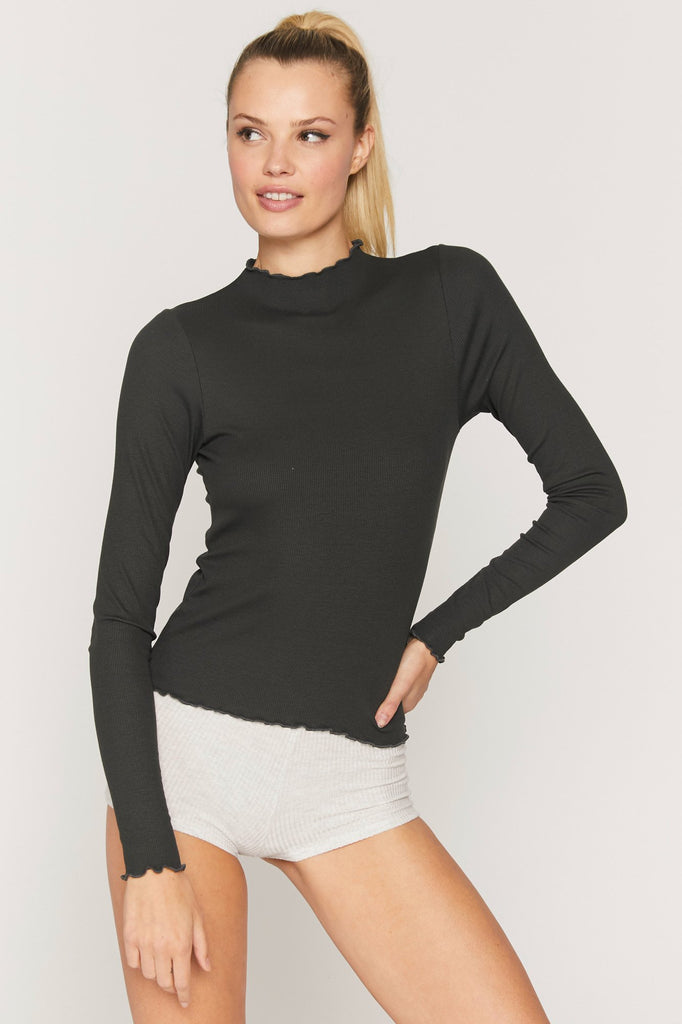 UNIKONCEPT Lifestyle boutique: image shows the Ruffle Mock Neck in black by Spiritual Gangster. This long-sleeve mock neck has subtle ruffle details along all of its hems (neck, bottom and sleeves. The fabric is ribbed and this style features a slim fit.