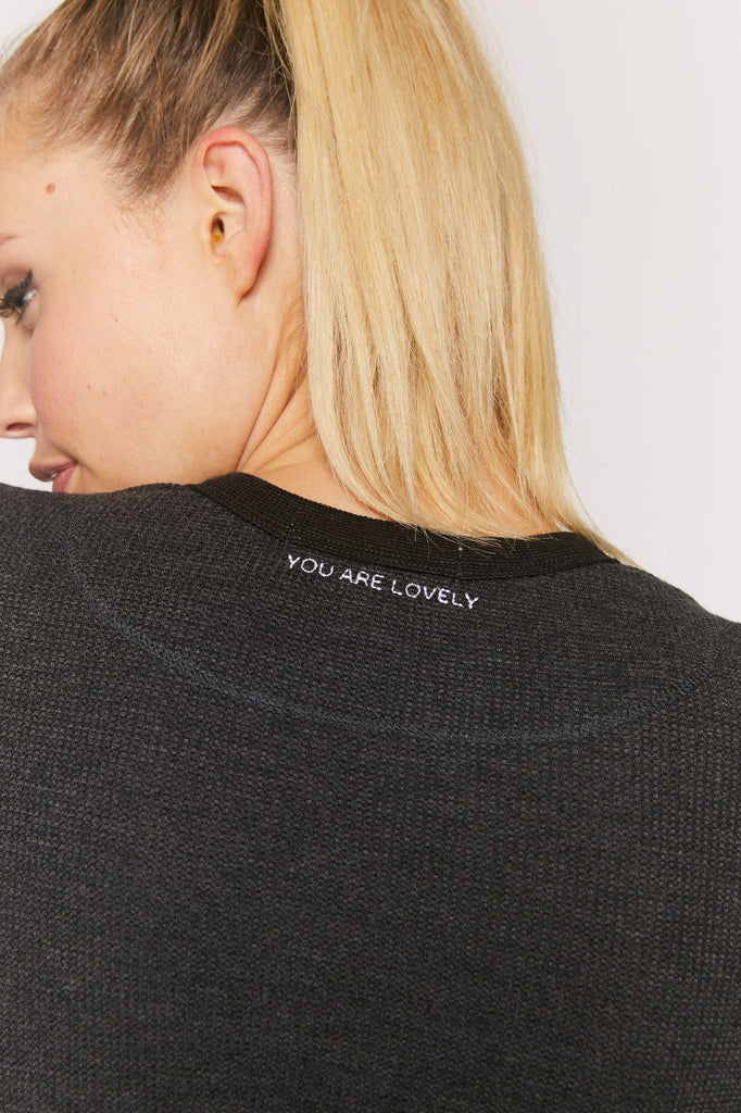 UNIKONCEPT: Lifestyle boutique; image shows a scoop neck longsleeve thermal with ruffled detailing at the bottom and thumb holes on wither sleeve. This thermal features spiritual gangsters signature affirmations at the back of the neck.