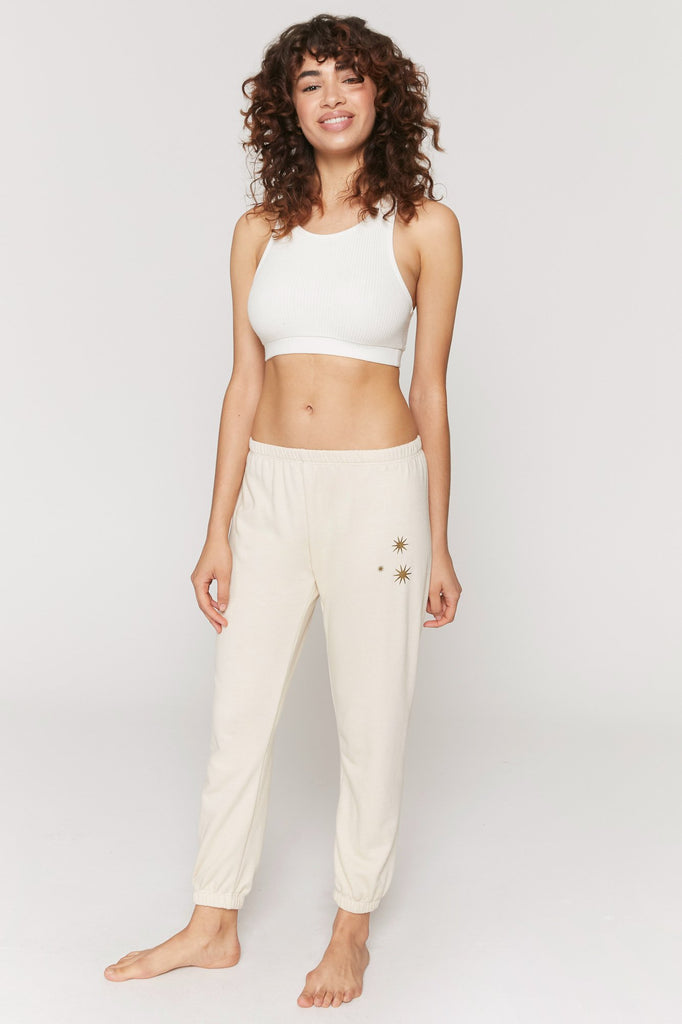 UNIKONCEPT Lifestyle boutique: image shows the Stars Perfect Sweatpants in cream by Spiritual Gangster. These sweats are tailored to provide a flattering slim fitting leg with an elasticized waist and ankles. The left leg of the sweats features a small star detail.