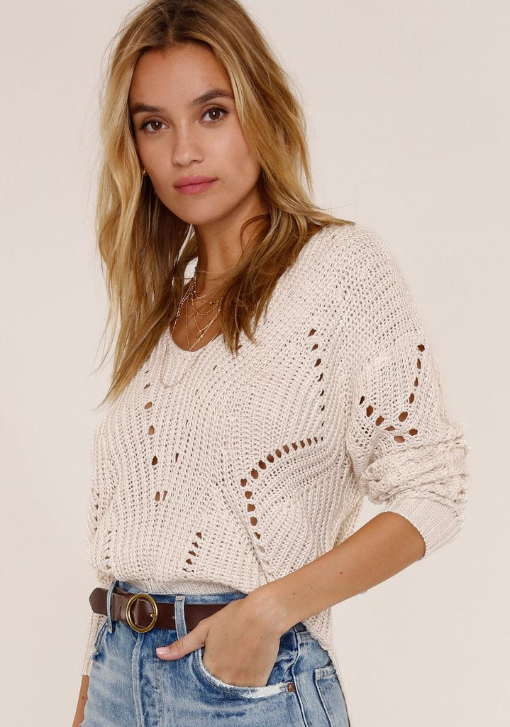 UNIKONCEPT Lifestyle boutique: Image shows the Camden Sweater in Ivory by Heartloom. This full length sweater is made of a crocheted knit pattern, perfect for transitioning between seasons. The bottom hem features two small slits up the side of the sweater. The neckline is a low cut v-neck.