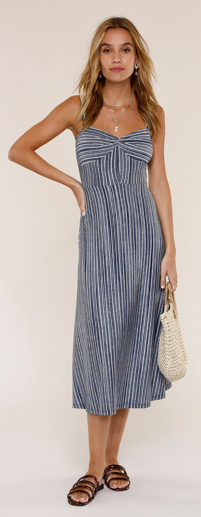 UNIKONCEPT: Lifestyle boutique; image shows a striped indigo and white dress by Heartloom. The Reese dress features a sweetheart neckline with a twisted middle of the bust section and thick adjustable straps. The dress is an a line style with a two dimensional stripe section. The top of the dress features stripes that are horizontal while the waistline down is vertical stripes