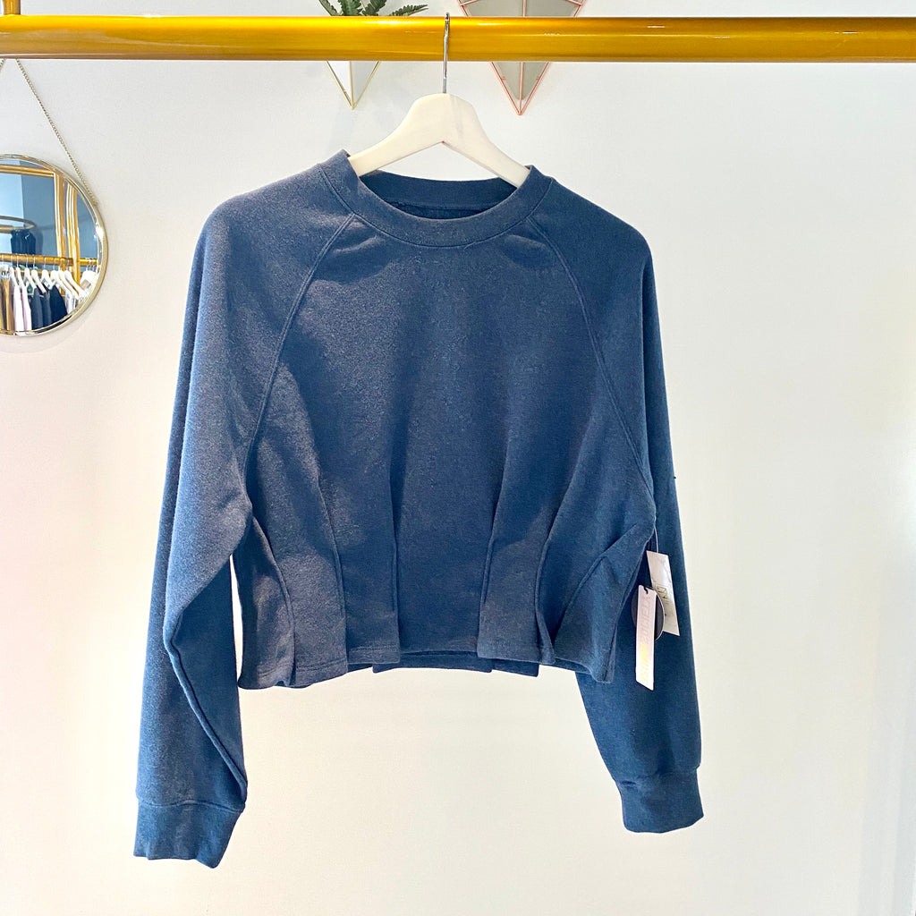UNIKONCEPT: Lifestyle boutique; image shows a navy blue coloured peplum sweater by Amuse society. The Devon peplum is a crewneck styled cropped sweater with small pleats around the waistline to give the illusion of a peplum cut.
