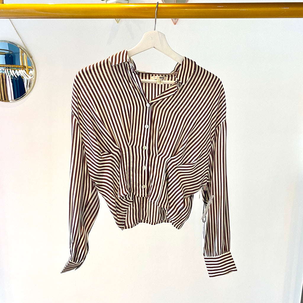 UNIKONCEPT: Lifetsyle boutique; image shows a long sleeve cropped button down blouse. The kala blouse features a collared neckline, red vertical stripes on a white base long sleeve, transparent buttons vertically placed and pleats along the tummy to keep the shirt down and allow it to billow perfectly.