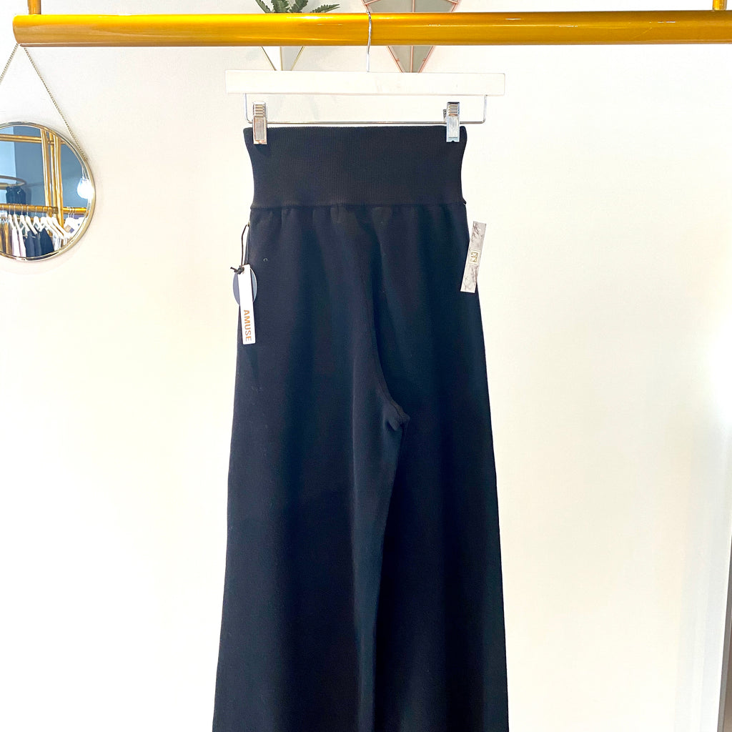 UNIKONCEPT: Lifestyle boutique; image shows a pair of black culotte style pant by amuse society. The mission pant features a high waisted elastic band and a thick black fabric that flares at the bottom of the pant.