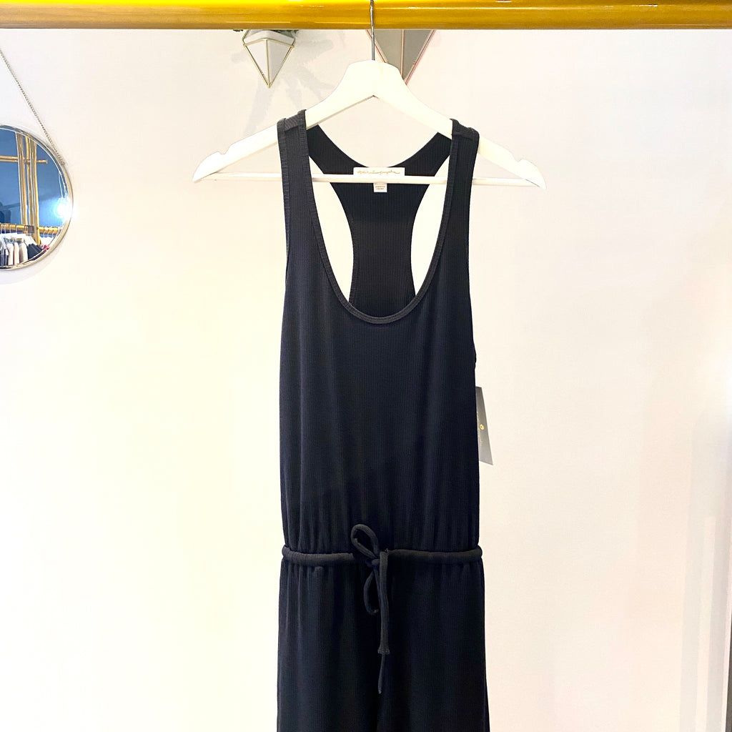 UNIKONCEPT: Lifestyle boutique; Image shows a razorback ribbed jumpsuit by spiritual gangster. The Giselle rib jumpsuit features a stretchy luxe ribbed material throughout, a sinched waistline with an elastic tie waistband and a tank styled razorback neckline. This jumpsuit is a skinny fit so it is comfortable and drapes perfectly over the body but the ankle is tight and fits perfectly to your calf.