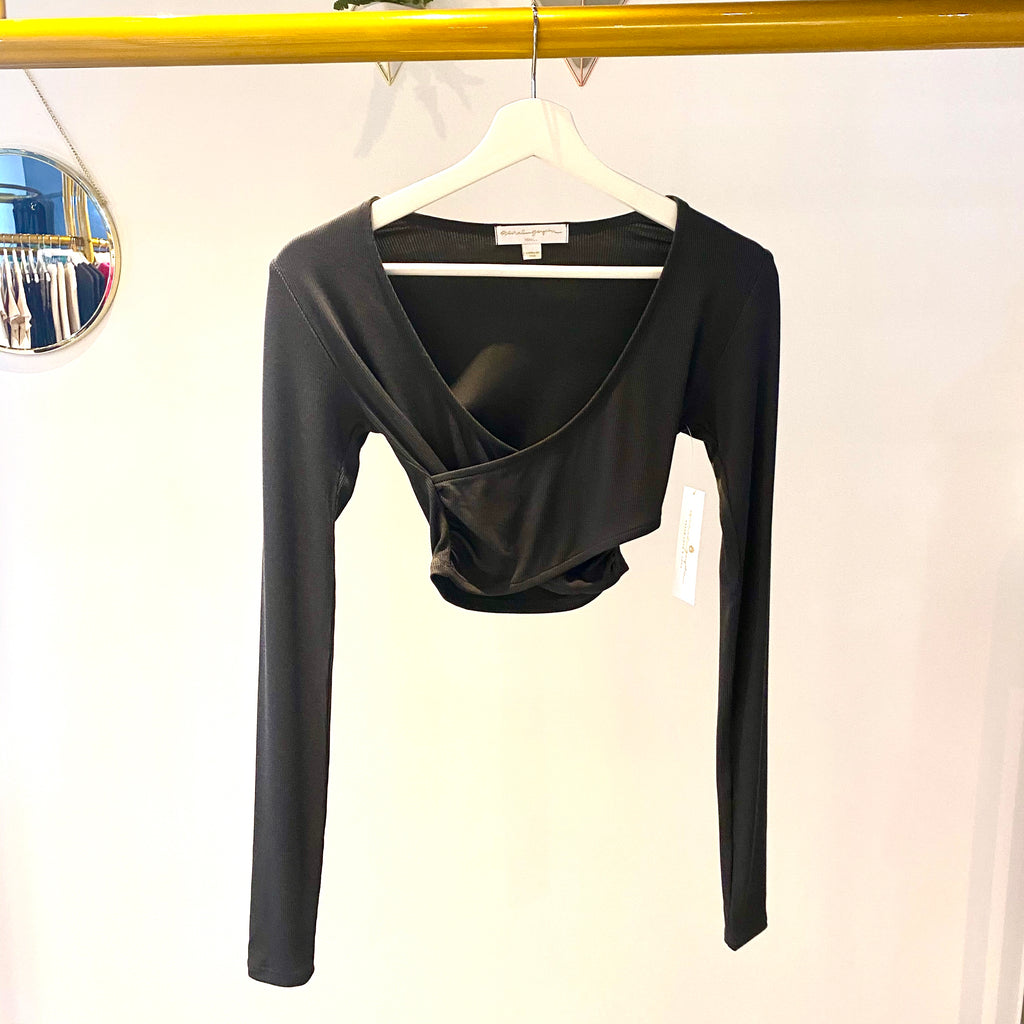 UNIKONCEPT: Lifestyle boutique; Image shows a ribbed long sleeve crop top by spiritual gangster. This vintage black coloured wrap crop top features full long sleeves, a v neckline and a two piece of fabric wrapped over top of eachother to give a criss crossed illusion.