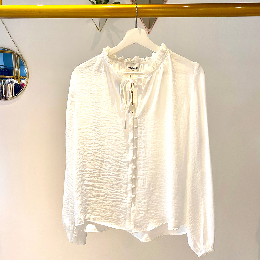 UNIKONCEPT: Lifesyle boutique; image shows a white long sleeve blouse by Heartloom. The Ellen top is a white blouse with vertical buttons and a tied neckline with small ruching around the collar