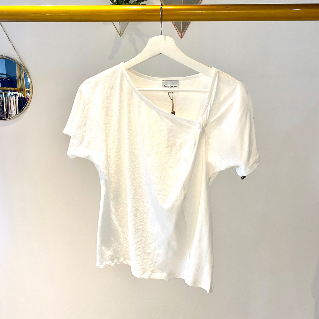 UNIKONCEPT: Lifestyle boutique; image shows a white short sleeve tee shirt by heartloom. The whyatt tee ia plain tee with a cute neckline detail. The left side features a small ruche.
