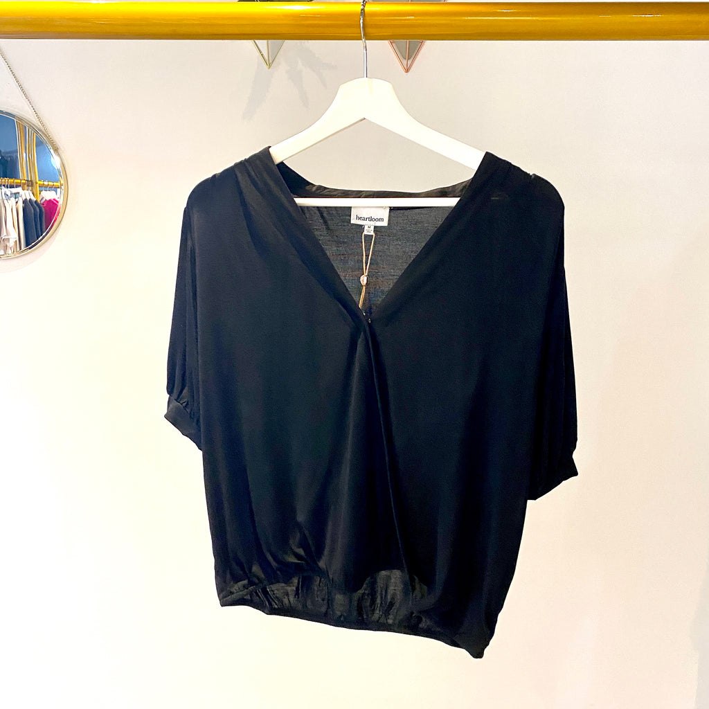 UNIKONCEPT: Lifestyle boutique; image shows a black short sleeved blouse by Heartloom. The Neo top features a v neckline with a slight plunge a button in the middle of the chest that creates a wrapped illusion and an elastic waistband to ensure the top stays put. There is also a small button on either dies of the sleeve for accent
