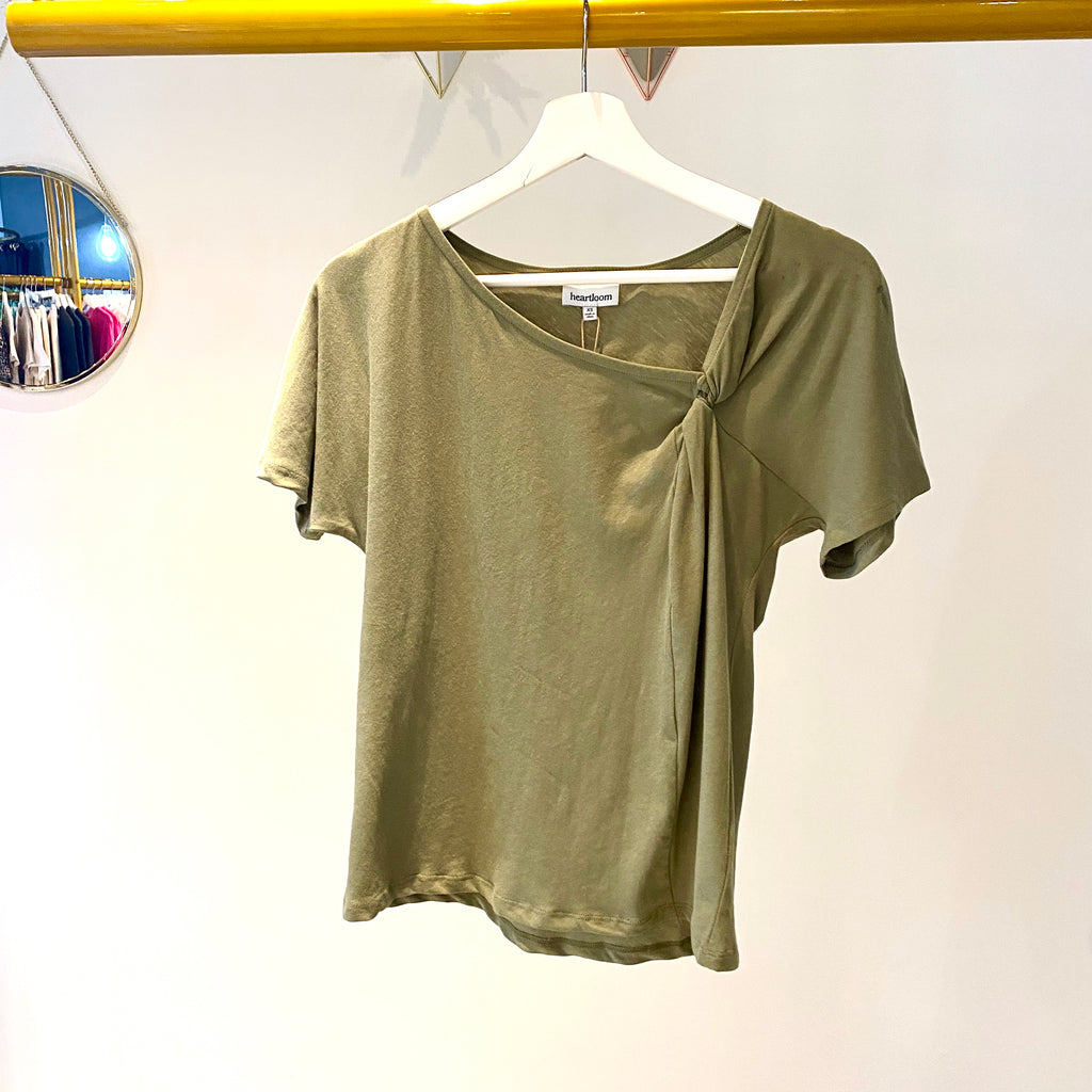 UNIKONCEPT: Lifestyle boutique; image shows an army green short sleeve tee shirt by heartloom. The whyatt tee ia plain tee with a cute neckline detail. The left side features a small ruche.